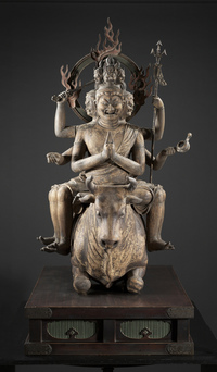 Life-size 13th-century wooden sculpture features a grimacing, multi-limbed Buddhist deity astride a kneeling bull. Clark Center for Japanese Art & Culture