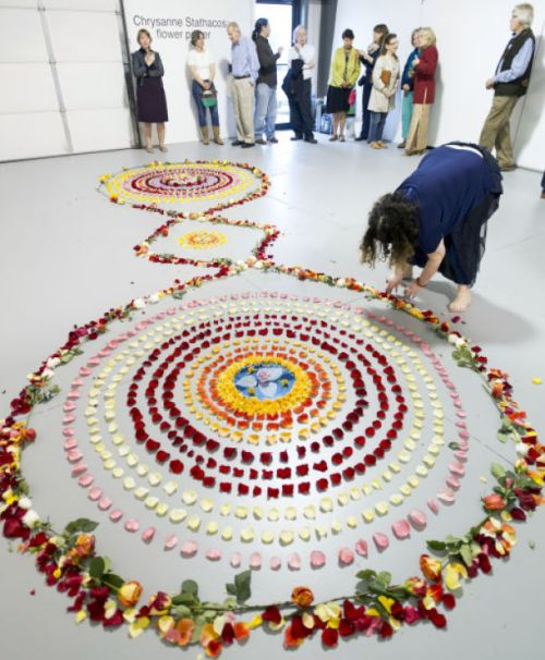 Artist Chrysanne Stathacos of New York puts the finishing touches on a double helix rose mandala for her Flower Power installation Saturday at Fiendish Plots exhibition space. The mandala is shown in conjunction with pictures, tapestries and poems to enhance the experience.