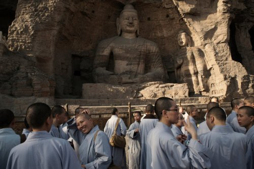 Buddhist nuns visited the Buddha statue at cave number 20 of the Yungang Grottoes. The front wall of the cave collapsed, exposing it to harmful elements. Credit Gilles Sabrie for The New York Times