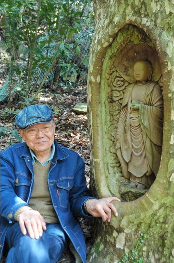 Fumiaki Ogita sits next to his Buddhist statuette he carved out of a live tree in Shikokuchuo, Ehime Prefecture. (Haruko Hosokawa)