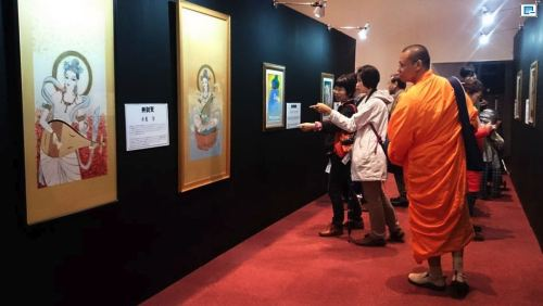 Visitors to Zojoji temple in Tokyo admire works by manga artists devoted to the theme of Buddha in an exhibition that continues until May 13. (Louis Templado)