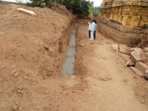 Officials inspecting the site where a Buddhist remains were unearthed at Bhimeswara Temple at Chebrolu in Guntur district. Photo: By Arrangement