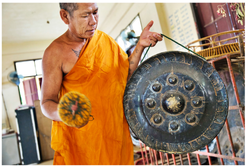 """Thailand's """"gong highway"""" starts 30 miles outside Ubon Ratchathani and ends in Khong Chiam, a fishing village on the cliffs of the Mekong River. Here, a Buddhist monk demonstrates strikes a…gong at a temple in Ubon Ratchathani Province. Credit Adam Ferguson for The New York Times"""
