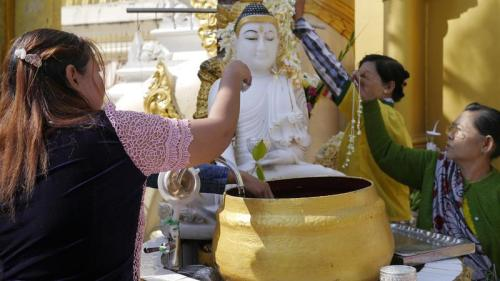 Burmese wash Buddha statues with fragranced water for good luck.  CREDIT DOUALY XAYKAOTHAO / KERA NEWS