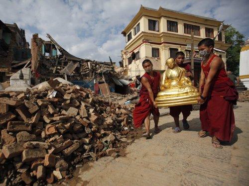 Buddhist monks recover a statue of a Buddhist deity from a monastery at Swayambhunath. Niranjan Shrestha/AP