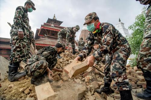 Picture of Nepalese security forces excavating ancient carvings and artifacts in Nepal Nepalese troops look for bodies at Patan Durbar Square. Looting at damaged and destroyed shrines and temples has been minimal, according to UNESCO officials. Bulldozers used to clear debris are a bigger threat.  PHOTOGRAPH BY BRIAN SOKOL, PANOS