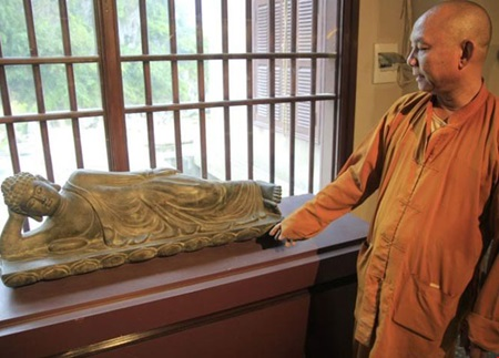 Reclining Buddha: Thich Hue Vinh, the abbot of Quan The Am Temple introducing a valuable antique which has been stored in his temple for a long time. — Photo thanhnien.vn