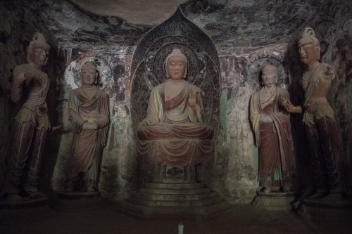 In a Mogao cave, lit by the flashlight of a guide, a Buddha statue surrounded by disciples dating from the Tang Dynasty. Dunhuang grotto art is a combination of architecture, painted sculpture and murals. (Gilles Sabrié/For The Washington Post)