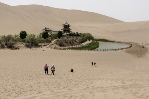 Tourists visit the Crescent Lake, one of Dunhuang's major tourist sites along with the Mogao caves. (Gilles Sabrié/For The Washington Post)