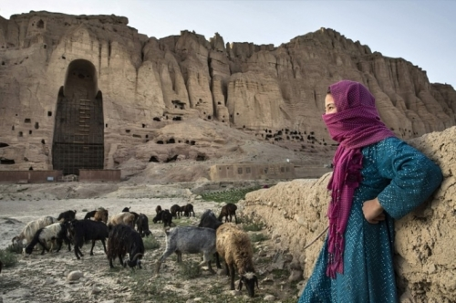A girl watches over her sheep and goats as they graze before one of the destroyed Bamiyan Buddhas. From wsj.com
